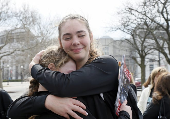 Hallie Vie Burton, a ball girl, left, and Jessica Bock, a player for West Branch, right, comfort each other outside St. John Arena after the OHSAA announced that all winter sports tournament postseason play was suspended on Thursday, March 12, 2020.   [Barbara J. Perenic/Dispatch]