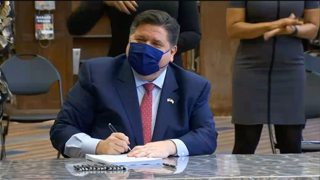 Gov. JB Pritzker gives House Bill 2170 his final signature, flanked by Lt. Gov. Juliana Stratton and members of the Illinois Legislative Black Caucus, during an event at Proviso East High School on Monday.
