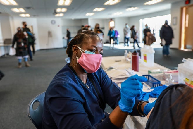 Registered Nurse Benita Rogers, 52, of Redford Twp administers the COVID-19 Pfizer vaccine at the Wayne County Community College District Downriver Campus in Taylor, Mich. on Feb. 6, 2021.