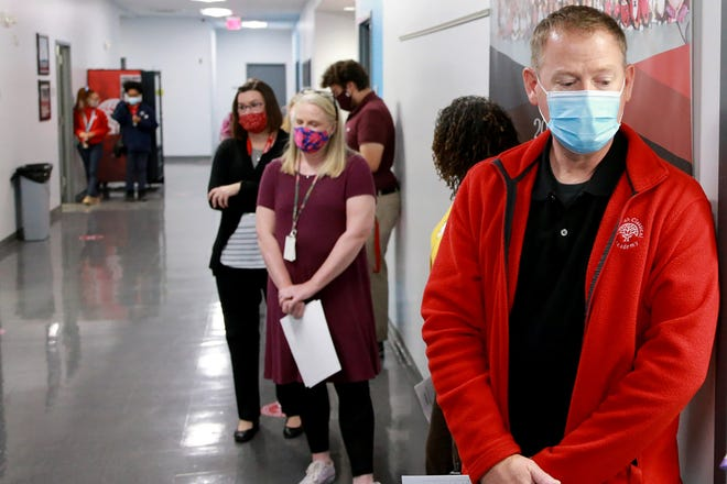 Savannah Classical Academy Executive Director Barry Lollis joins his fellow faculty and staff members as they prepare to receive the COVID-19 vaccine Monday morning.