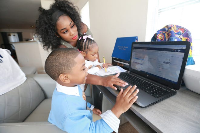 Azia Thurmond gives her son Alexus, age 6, a hand with his first grade virtual lesson while her daughter Millie draws at the desk.