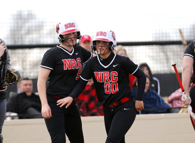 North Rock Creek's Katie Larson (00) and Haley Hacker (9) celebrate after Larson hit the first slow pitch home run in school history against Wellston Friday. It was also the Lady Cougars' first slow pitch victory.