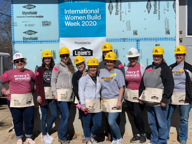 A group of women stand in front of a home build during the 2020 International Women Build Week hosted by Habitat for Humanity.