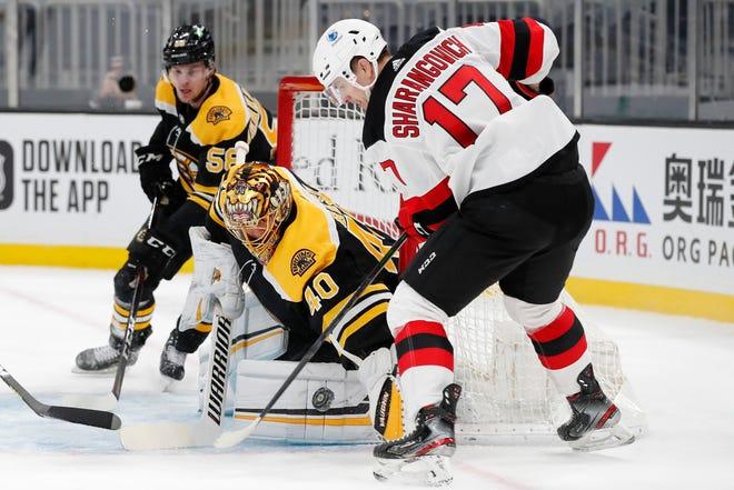 Boston's Tuukka Rask blocks a shot by New Jersey's Yegor Sharangovich (right) during Sunday's game.