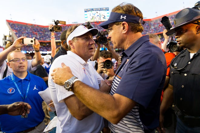 Florida head coach Dan Mullen, left, greets then Auburn coach Gus Malzahn at the end of the game on Oct. 5, 2019 at Ben Hill Griffin Stadium.