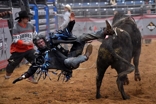 Caleb Christian of Arlington falls to the arena floor after getting bucked off of Little Voodoo Jacket Saturday. It was the first time for American Bucking Bull, Inc. to hold its Spring Fling PBR Bull Riding competition at the Taylor Telecom Arena at the Expo Center of Taylor County.