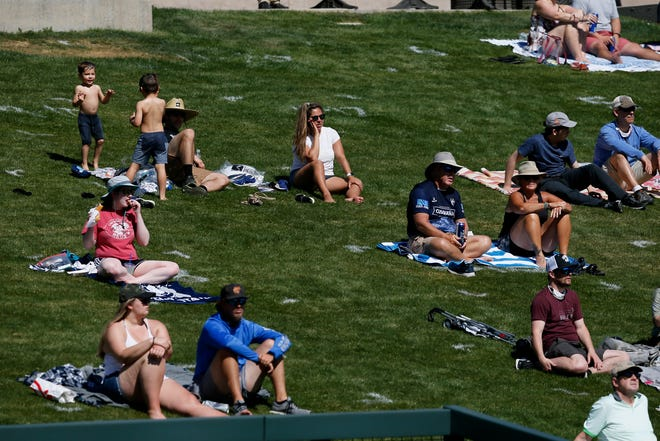 Fans watch from the lawn seats in the fourth inning of the MLB Cactus League Spring Training game between the Colorado Rockies and the Cincinnati Reds at Salt River Fields in Scottsdale, Ariz., on Monday, March 8, 2021.