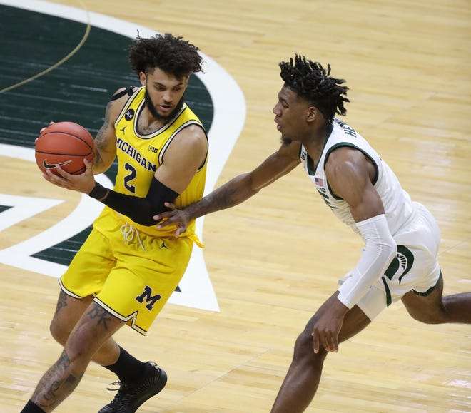 Michigan State Spartans forward Aaron Henry (0) defends against Michigan Wolverines forward Isaiah Livers (2) on Sunday, March 7, 2021, at the Breslin Center in East Lansing.
