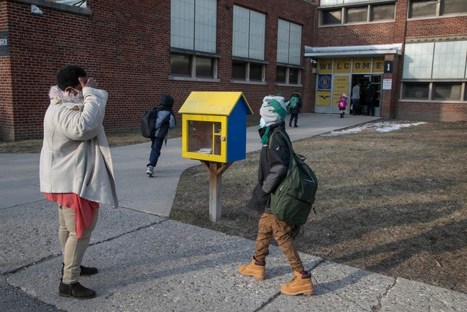 Social worker Tonya Pittman, left, screens students about how they feel before they enter Warren E. Bow Elementary School in Detroit for in-class learning Monday Mar. 8, 2021 as the state lifts the lockdown ban on students and teachers.