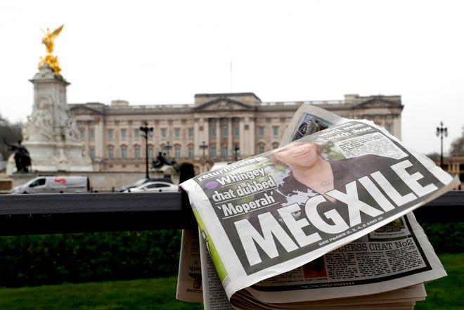 Sebuah surat kabar tertiup angin setelah ditempatkan di pagar oleh kru televisi di luar Istana Buckingham di London, Senin, 8 Maret 2021.