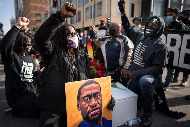 Cortez Rice, left, of Minneapolis, sits with others in the middle of Hennepin Avenue on Sunday, March 7, 2021, in Minneapolis, Minn., to mourn the death of George Floyd.