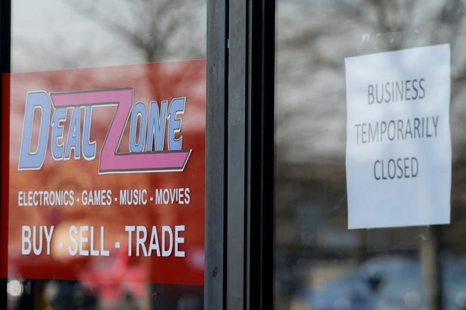 """""""Business temporarily closed"""" reads a sign posted on the door of Deal Zone, 100 South Creasy Lane, Monday, March 8, 2021 in Lafayette"""