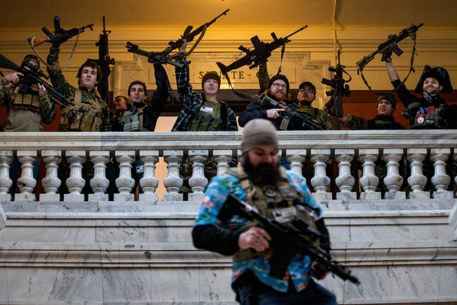 Gun rights supporters hold up their assault rifles on the second floor inside the Kentucky state Capitol, just outside the Senate chambers, during a Second Amendment rally in Frankfort, Ky. on Friday. Jan. 31, 2020