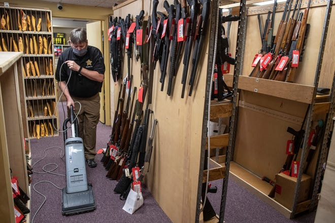 Rick Harrison, the administrative assistant to the sheriff, vacuums inside the Jefferson County Sheriff's Office property room, where confiscated weapons are held. Typically, before the COVID-19 pandemic, 2,000 to 2,500 guns were held there. March 1, 2021