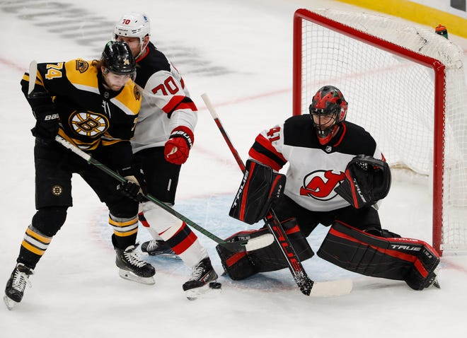 March 7, 2021; Boston, Mass. -- Boston Bruins left wing Jake DeBrusk (74) tries to deflect a shot on New Jersey Devils goaltender Scott Wedgewood (41) during the first period at TD Garden.