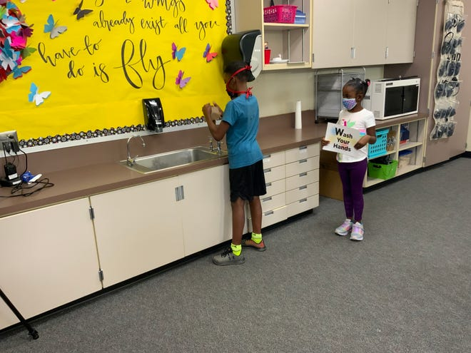 Brother and sister Quinten and Kanadii, students at Harry S. Truman Elementary School, demonstrate how to WASH hands as they help create a back to in-person learning video.