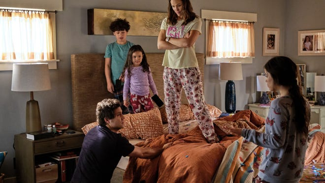 Entire family on the morning of Yes Day. Allison and two of the children stand on the bed, while Carlos kneels next to it and their other daughter stands in front of it.