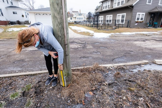 Anne Trombley measures a marker set by an inspector to show the new flood level outside of her Algonac home Thursday, March 4, 2021. The mark was about 20 inches above the ground.