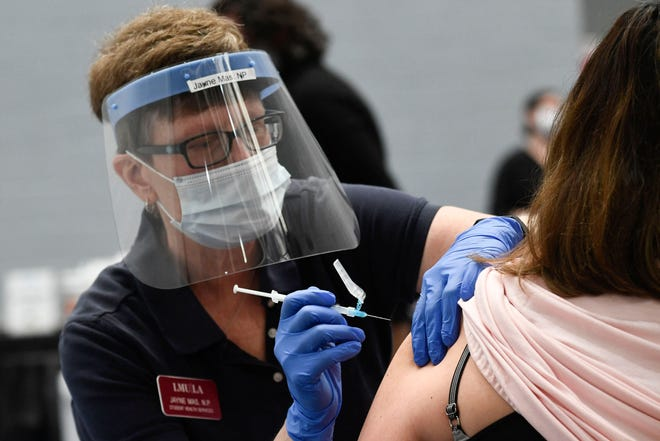 A nurse practitioner administers a dose of the Moderna Covid-19 vaccine at a clinic for Catholic school education workers including elementary school teachers and staff at a vaccination site at Loyola Marymount University in Los Angeles on March 8.