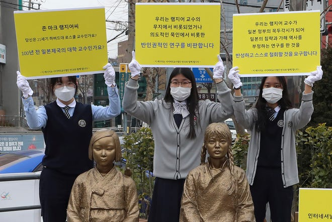 "In this Feb. 25, 2021, photo, high school students hold up banners to protest a recent academic paper by Harvard University professor J. Mark Ramseyer, behind statues symbolizing wartime sex slaves in Seoul, South Korea. The signs read: ""J. Mark Ramseyer, are you a 21st century professor at Harvard? Are you a university professor in the Japanese Empire 100 years ago? We criticize anti-human rights research."""