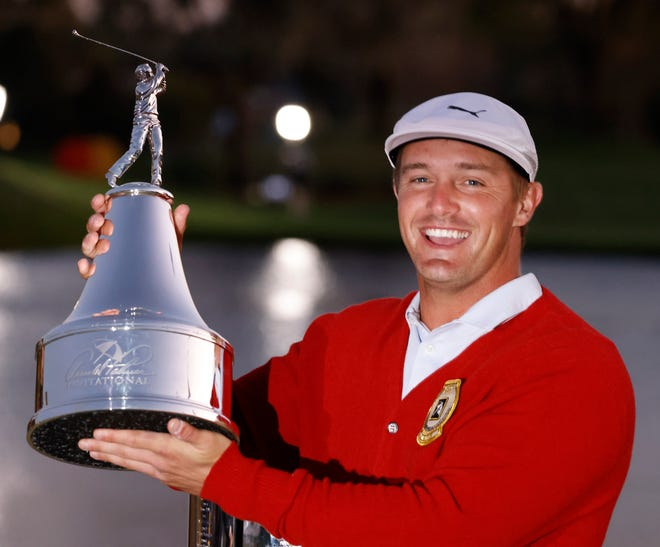 Bryson DeChambeau holds the champions trophy after winning the Arnold Palmer Invitational golf tournament at Bay Hill Club & Lodge in Orlando on Sunday.