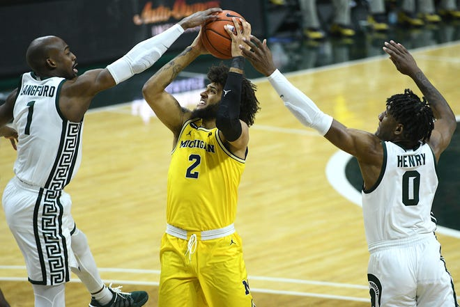 Michigan Wolverines forward Isaiah Livers (2) goes to the basket as Michigan State Spartans guard Joshua Langford (1) and forward Aaron Henry (0) defend during the first half at Jack Breslin Student Events Center.