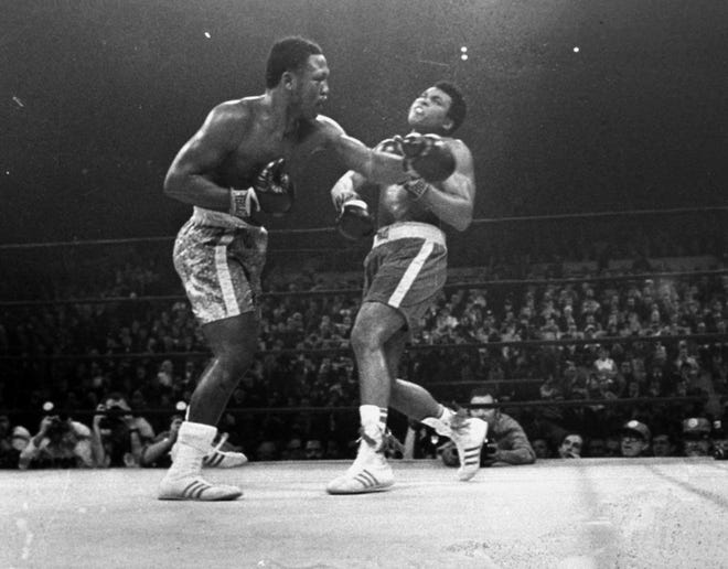 Joe Frazier hits Muhammad Ali with a left during the 15th round of their heavyweight title fight on March 8, 1971.