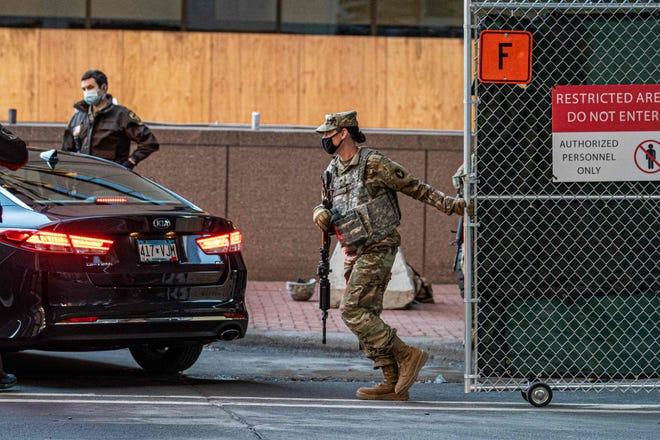 Members of the National Guard close the gates at the Hennepin County Government Center before jury selection begins in the trial of former Minneapolis police officer Derek Chauvin on March 8.