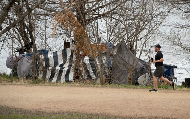 A homeless camp is on the shore of Lady Bird Lake next to the Ann and Roy Butler Hike and Bike Trail on South Lakeshore Boulevard on Tuesday March 9, 2021.