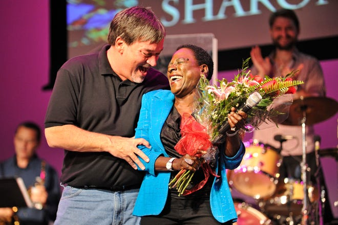 """Augusta native Sharon Jones is presented with flowers by Ed Turner after joining Ed Turner and Number 9 on stage to perform the James Brown hit song """"It's a Man's Man's Man's World"""" during the band's Rock & Soul Revue at the historic Imperial Theatre on Friday, Aug. 8, 2014."""