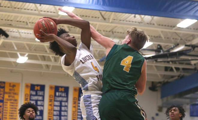 Lincoln Park's L.A. Pratt attempts a layup while being guarded by Deer Lake's Derek Burk during the first half of the WPIAL 3A Playoffs Monday night at Lincoln Park Performing Arts Charter School.