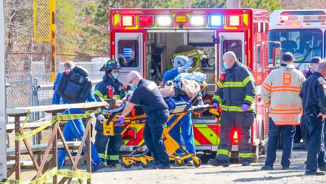 Fire officials attend to a man who severely injured his hand at an address on Portside Drive in Pocasset Tuesday afternoon. The man was taken by MedFlight to Rhode Island Hospital. [Dave Curran]