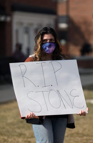 BGSU student Maya Elias holds a sign during a protest  outside Pi Kappa Alpha at Bowling Green State University on Tuesday, March 9, 2021. Stone J. Foltz, 20, of Delaware, Ohio, Foltz died Sunday, three days after an alleged off-campus hazing incident.THE BLADE/AMY E. VOIGT