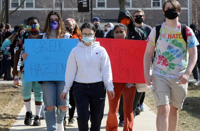 A Bowling Green State University student leads students across campus to the to McFall Center during a protest in honor of Stone Foltz, 20, who died after an alleged hazing incident.