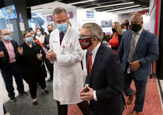 Alongside the Ohio State Wexner Medical Center CEO Harold Paz, Gov. Mike DeWine tours the COVID-19 mass vaccination facility set up at Ohio State's Schottenstein Center in Columbus on Tuesday, March 9, 2021.
