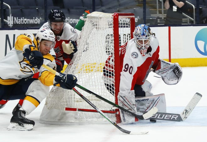 Elvis Merzlikins stuffs a wrapround attempt by Nashville's Luca Sbisa on Feb. 20, before the Blue Jackets goaltender was injured after getting tied up with the Predators' Viktor Arvidsson.