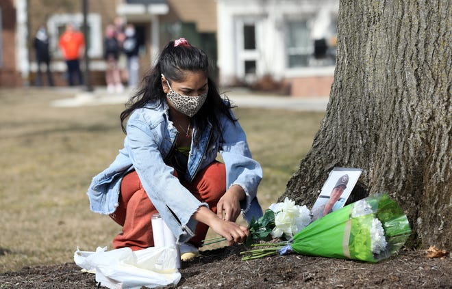 A BGSU student, who did not want to be identified, places candles at a makeshift memorial to honor Stone J. Foltz, 20, of Delaware, Ohio, outside Pi Kappa Alpha at Bowling Green State University on Tuesday, March 9, 2021. Foltz died Sunday, three days after an alleged off-campus hazing incident.THE BLADE/AMY E. VOIGT