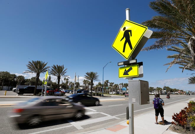 Cars whiz by a crosswalk on Atlantic Avenue in Daytona Beach on Tuesday, March 9, 2021.
