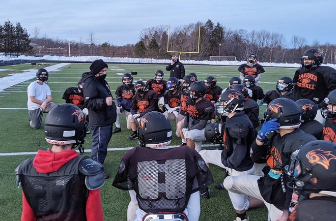 Gardner High football coach Sean Whittle, left, talks to his team at the end of practice earlier this month at Watkins Field.