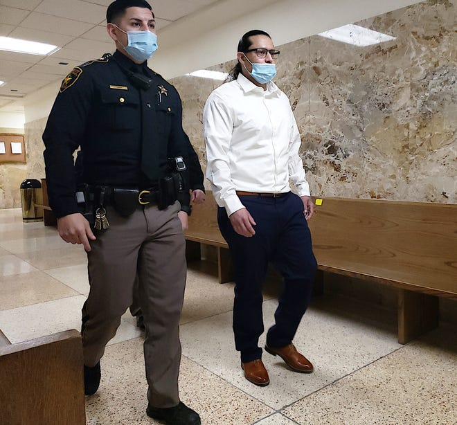 Isaias Cabello is escorted by a Lubbock County sheriff's deputy out of a courtroom Tuesday during his murder trial in connection with a 2015 fatal shooting in East Lubbock. Prosecutors moved to dismiss his case later that day.