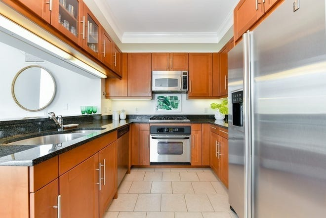 City chic rules in the spacious U-shaped kitchen with a substantial amount of timeless Poggenpohl cabinetry, anchored by granite countertops and accented by stainless steel appliances that include a four-burner gas Viking range.