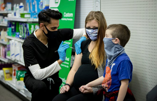Skippack Pharmacy owner and pharmacist Dr. Mayank Amin administers vaccine to Aubrie Cusumano while son Luca watches on Feb. 11, 2021, in Skippack, Pennsylvania. In communities across the country, local pharmacy owners are among the people administering COVID-19 vaccinations. [BP Miller/Chorus Photography via AP]