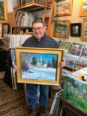 Millbury artist Mike Graves in his studio with one of his paintings.