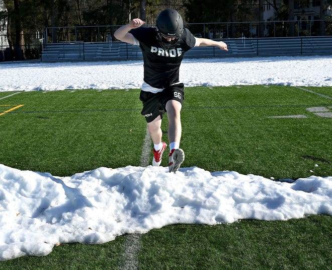 Wellesley's Will Hutzler jumps over a mound of snow during warm-ups at practice on March 9, 2021.