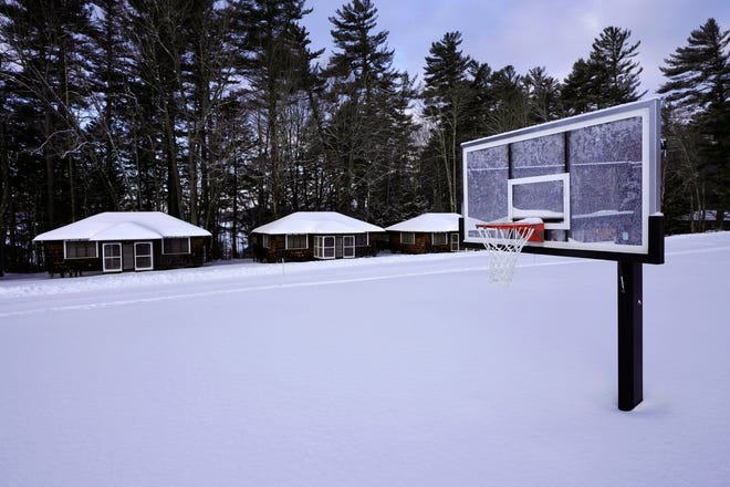 Snow covers a basketball court at Camp Fernwood, a summer camp for girls, Saturday, Feb. 20, 2021, in Poland, Maine. Camp directors across the country are feeling more confident about reopening this summer after a pandemic hiatus in 2020, but in some states they are still awaiting guidelines. (AP Photo/Robert F. Bukaty)