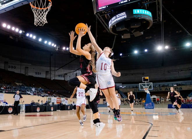 Tuttle's Madi Surber (4) goes to the basket past Holland Hall's Mia Fugate (10) during a Class 4A Girls quarterfinal on Tuesday at State Fair Arena in Oklahoma City.