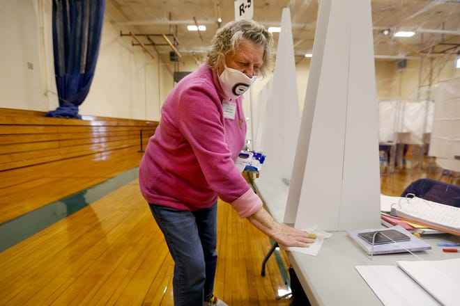 Exeter ballot clerk Carole Smith sanitizes her station with a wipe on Tuesday, March 9, 2021 during town elections.