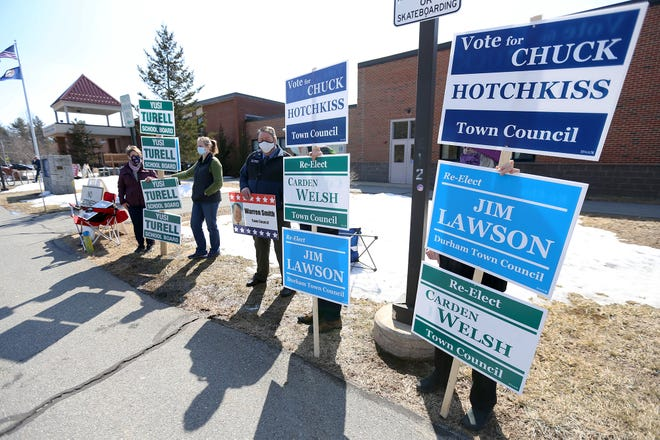 Campaign volunteers hold signs outside of Oyster River High School on Tuesday afternoon during the Durham town elections.