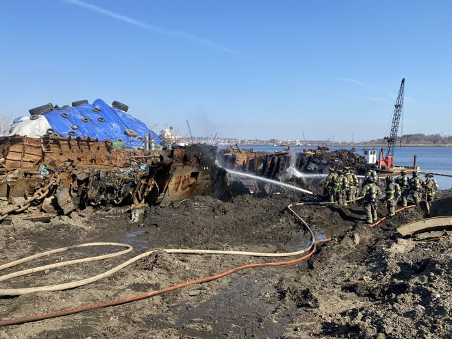 Firefighters douse the remnants of an old Russian submarine that caught fire Tuesday morning at a Providence scrapyard.