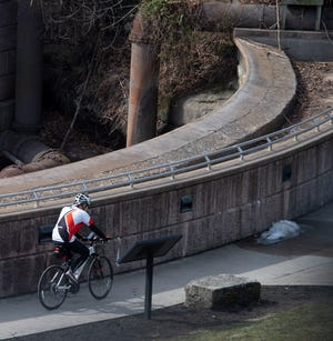 A cyclists takes advantage of mild weather at Franklin Mills Riveredge Park in downtown Kent.